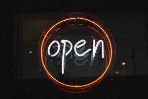 Neon sign in a dark window, reading 'open'