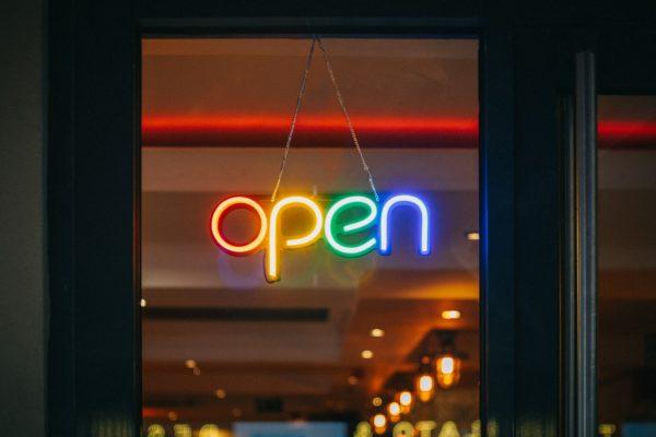 Multicoloured neon sign reading 'open'