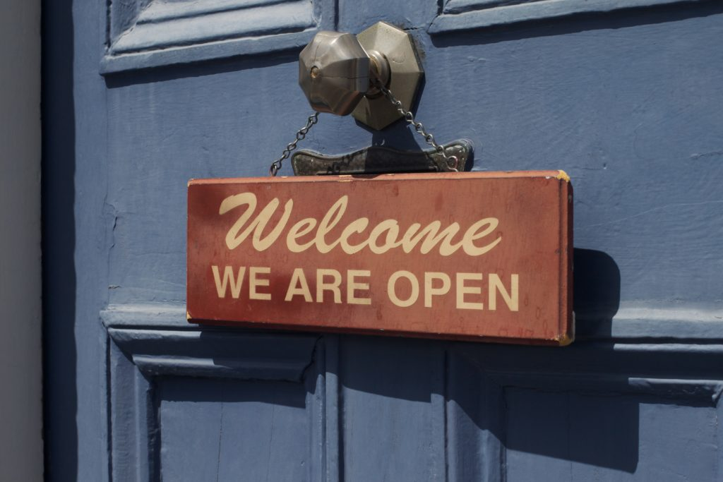 """Small sign on blue door reading """"Welcome, we are open"""""""